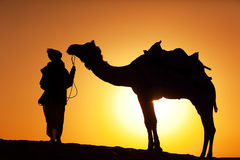 Man and camel silhouette stock photo