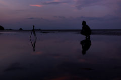 Man and camera on the beach with reflection in water during suns Stock Photos