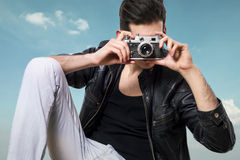Man camera. Fashion shot of a man taking a photo with a vintage camera Royalty Free Stock Photography