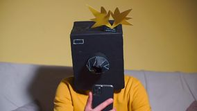A man in a camera mask on his head uses a new smartphone at a masquerade party.