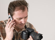 Man with camera and phone Stock Images