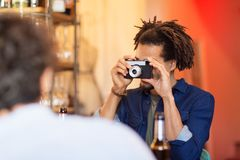 Man with camera photographing friend at bar. Technology, lifestyle and people concept - men with camera photographing friend at bar Royalty Free Stock Photos