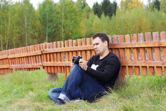 Man with camera sits on grass near orange wooden fence Stock Images