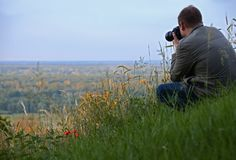 the man with the camera sits on a high green hill next to the red poppy flowers royalty free stock images