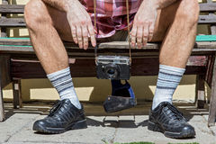 Man with camera sitting on a bench. Legs of man sitting on a bench Stock Image