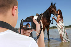 Man with camera taking picture of young beautiful woman on the h Royalty Free Stock Image