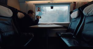Man stocker shooting landscape from moving train. Man with camera taking video of passing snowy pinery landscape when traveling in first class carriage of stock footage