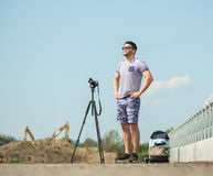Man with camera on tripod. Man with photo camera on tripod taking timelapse photos in the city Royalty Free Stock Photos