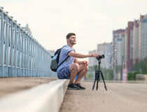 Man with camera on tripod. Man with photo camera on tripod taking timelapse photos in the city Royalty Free Stock Photography