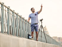 Man with camera on tripod. Man with photo camera on tripod taking timelapse photos in the city Stock Images