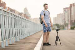 Man with camera on tripod. Man with photo camera on tripod taking timelapse photos in the city Stock Photo