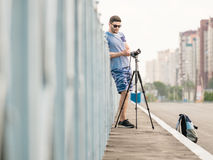 Man with camera on tripod. Man with photo camera on tripod taking timelapse photos in the city Royalty Free Stock Images
