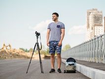 Man with camera on tripod. Man with photo camera on tripod taking timelapse photos in the city Stock Photos