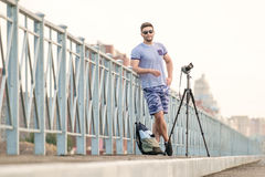 Man with camera on tripod. Man with photo camera on tripod taking timelapse photos in the city Stock Image