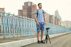 Man with camera on tripod. Man with photo camera on tripod taking timelapse photos in the city Royalty Free Stock Photo