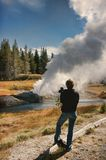 Man with a camera watching riverside geyser erupt. Man with a camera watching rivere geyser erupt, retro look in Yellowstone National Park stock image