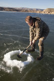 Man in camo chopping hold in ice with axe down Stock Images