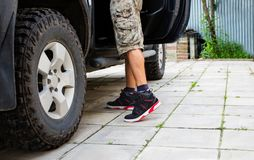 Man in camo shorts standing next to the truck with open door. Man in camo shorts and high-top sneakers standing next to the truck with open door, daytime Stock Photography
