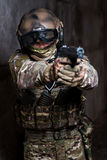 Man in camouflage aiming from gun. Military man in camouflage aiming from gun In full ammunition and camouflage - in a helmet, goggles, gloves, headphones royalty free stock photos