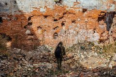 Man in camouflage with a backpack is walking along ruins of city. Post apocalyptic concept Stock Photo