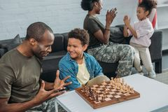 Man in camouflage clothes teaching his son to play chess while mother and daughter. Playing together stock images