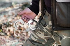 Man in camouflage fatigues holding handcuffs. Displayed in his hand in a concept of law enforcement royalty free stock photos