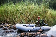 Man in camouflage fishing rod on the river. Man in camouflage fishing rod on the river on a rubber boat royalty free stock images