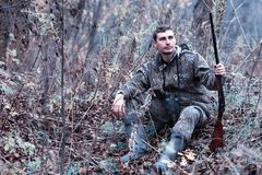 A man in camouflage and with a hunting rifle in a forest on a sp. Man in camouflage and with a hunting rifle in a forest on a spring huntr royalty free stock image