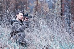 A man in camouflage and with a hunting rifle in a forest on a sp Royalty Free Stock Photography