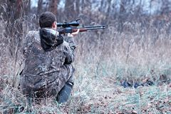 A man in camouflage and with a hunting rifle in a forest on a sp. Man in camouflage and with a hunting rifle in a forest on a spring huntr royalty free stock photo