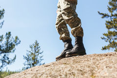 A man in camouflage old shoes with spikes for climbing on rocks. Trikoni. Tricouni. Standing on a cliff Stock Image