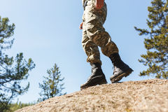 A man in camouflage old shoes with spikes for climbing on rocks. Trikoni. Tricouni. Standing on a cliff Stock Photos