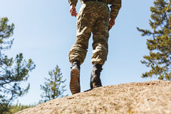 A man in camouflage old shoes with spikes for climbing on rocks. Trikoni. Tricouni. Royalty Free Stock Image