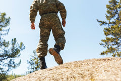 A man in camouflage old shoes with spikes for climbing on rocks. Trikoni. Tricouni. Standing on a cliff Stock Photo