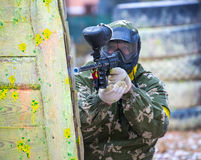 Man in camouflage with paintball gun behind fortification. Outdoors Stock Photos