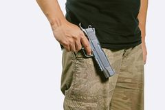 Man in a camouflage pants holding a gun isolated on white background. Army, Semi-automatic handgun, 45 pistol royalty free stock photo