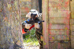 Man in camouflage shooting from paintball gun Stock Photos