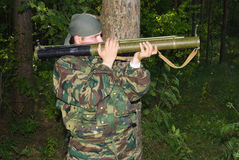 Man in a camouflage shoots from a grenade launcher. Young man in a camouflage shoots from a grenade launcher Stock Photos