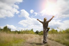 Man in camouflage is staying on green grass in the park with face and hands raised up to sky and eyes closed on sunny summer day. Concept of meditation royalty free stock images