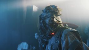 Man in camouflage suit with lights on neck dances at night club halloween party stock footage