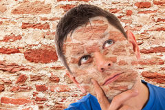 Man camouflaged in front of a wall Stock Photos