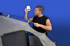 Man camping. Man surprised and angry looking at empty cup over blue background Stock Image