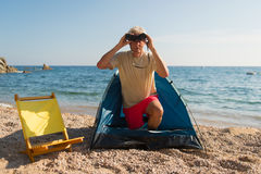 Man camping at the beach. Man with spy glasses camping at the beach royalty free stock photography