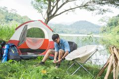 Man camping by the lake. Asian man camping by a lake and sitting enjoying the view stock photo