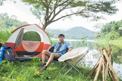 Man camping by the lake. Asian man camping by a lake and sitting enjoying the view stock images