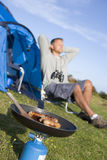 Man camping outdoors and cooking Royalty Free Stock Photos