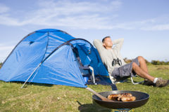 Man camping outdoors and cooking. Man camping outdoors relaxing with food cooking royalty free stock image
