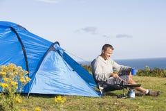 Man camping outdoors and cooking. Man camping in a field outdoors and cooking royalty free stock photos