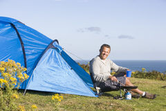 Man camping outdoors and cooking. Man camping outdoors, cooking and smiling at camera stock photos
