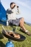 Man camping outdoors and cooking.  royalty free stock images